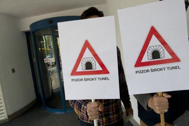 Dvojica držží transparenty s nápisom ´Pozor šŠiroký tunel´ počas schôdze veriteľov. Foto - TASR