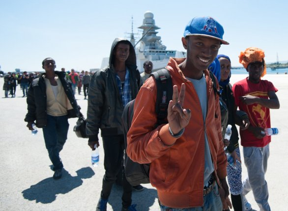54e0a5573e4e7 Zachránený africký imigrant ukazuje znak víťazstva po vylodení z  talianskeho námorného plavidla Bettica v sicílskom prístave