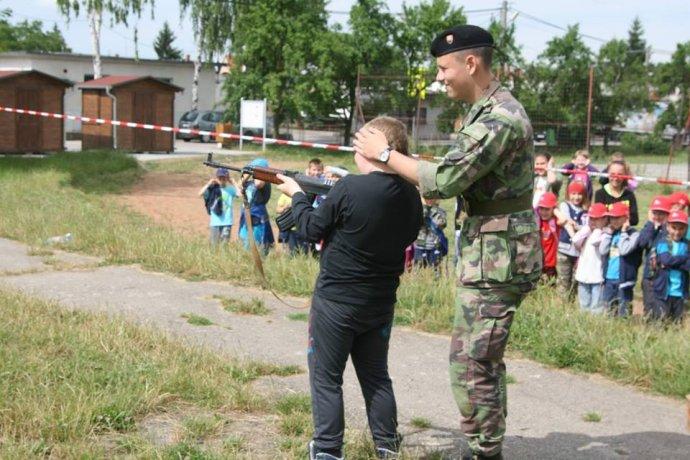 Švrček na fotke z roku 2015 učí deti na základnej škole v Ludaniciach strieľať slepými zo samopalu. Foto – Slovenskí branci