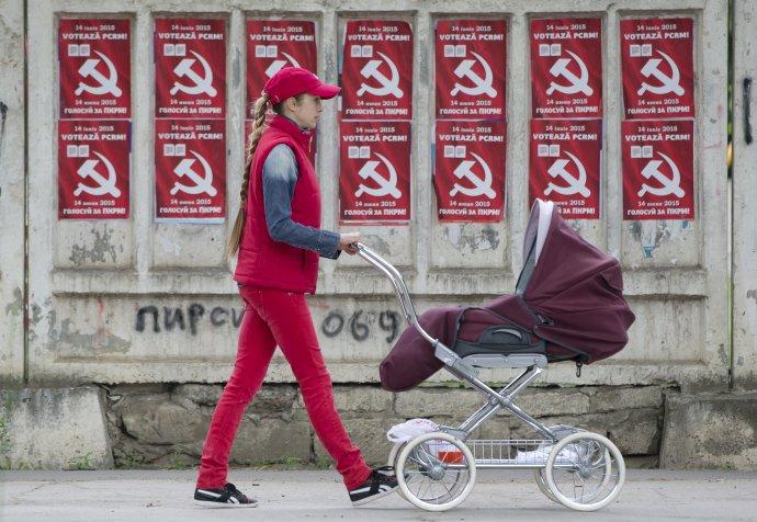 Žena tlačí kočík okolo plagátov moldavskej komunistickej strany v Kišiňove. Foto – TASR/AP