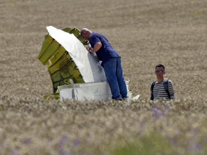 Malajzijskí leteckí vyšetrovatelia skúmajú trosky lietadla Boeing 777 na mieste dopadu pri obci Hrabove na východe Ukrajiny. FOTO - TASR/AP