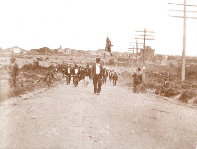 Jedna z mála fotiek z masakry. Baníci pochodujúci do Lattimera si vzali so sebou aj americkú zástavu, ktorú niesol Slovák Steve Jurich. Zdroj – Pennsylvania State Archives