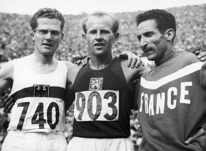 Na archívnej snímke z 24. júla 1952 zľava Nemec Herbert Schade, Emil Zátopek z Československa a Francúz Alain Mimoun pózujú v cieli po pretekoch na 5 000 metrov na letnej olympiáde na Olympijskom štadióne v Helsinkách. Zlatú olympijskú medailu získal Emil Zátopek, ktorý do cieľa dobehol v novom olympijskom rekorde 14:06:6 minút. Foto – TASR/AP