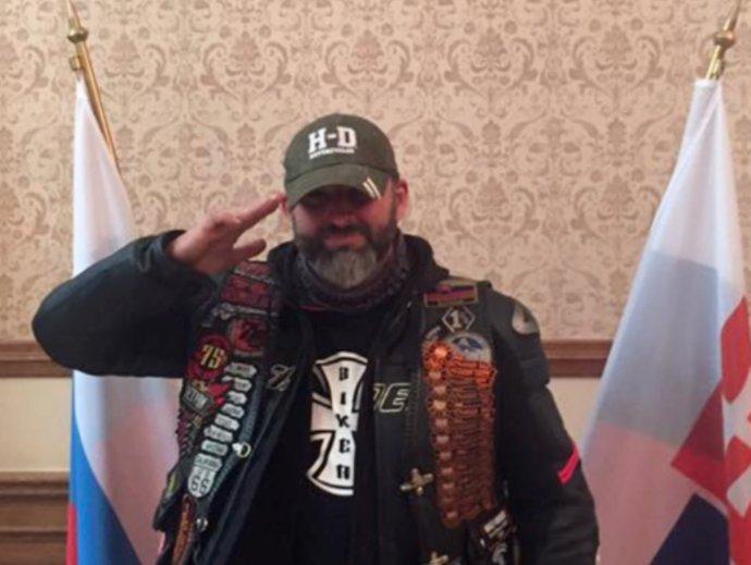 Jozef Hambálek, ktorý salutuje pred ruským štátnym znakom, pravdepodobne v priestoroch ambasády. Foto – FB J. Hambálka
