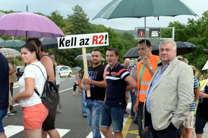 """Árpád Érsek (vpravo) ešte ako minister dopravy na protestnom blokovaní dopravy pod horským priechodom Soroška v roku 2017. Maďarský nápis na transparente hovorí: """"R2 je potrebná!"""" Foto - TASR"""