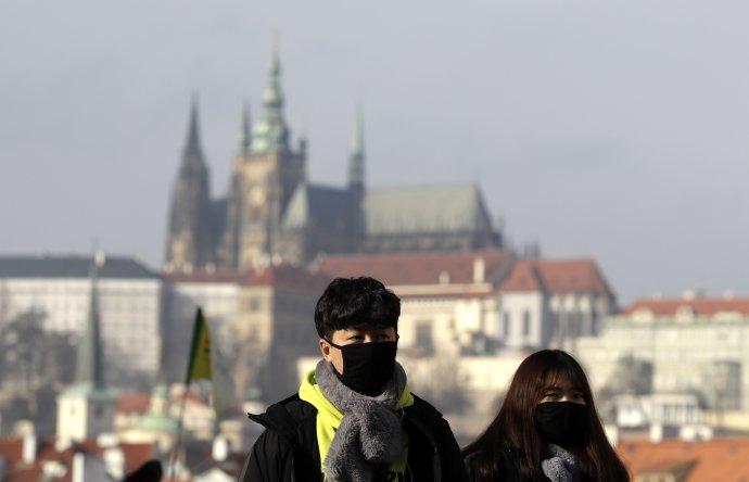 Turisti majú na tvári ochranné rúška počas návštevy Karlovho mosta v Prahe. Foto - tasr/ap