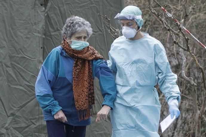 Talianska lekárka podopiera staršiu chorú pacientku. Foto - TASR/AP