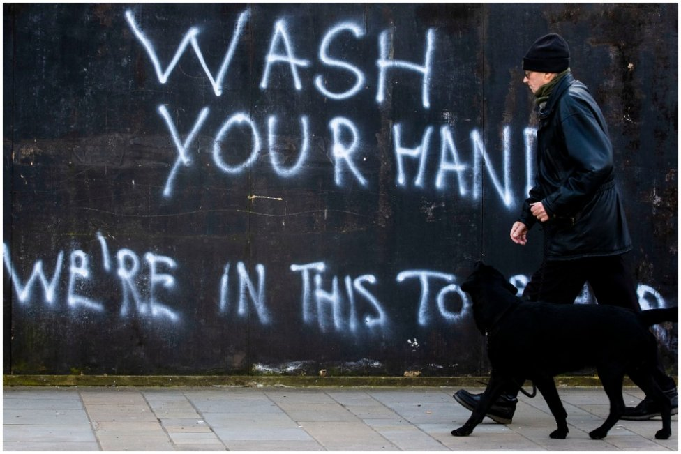 """Muž na prechádzke so psom prechádza okolo nápisu """"Umývaj si ruky, sme v tom spoločne"""" na ulici v severoírskom Belfaste. Foto - TASR/AP"""