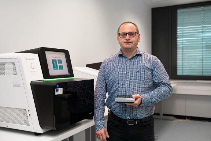 Tomáš Szemes vedľa sekvenátora v laboratóriu vo Vedeckom parku UK. Foto – archív T. S.