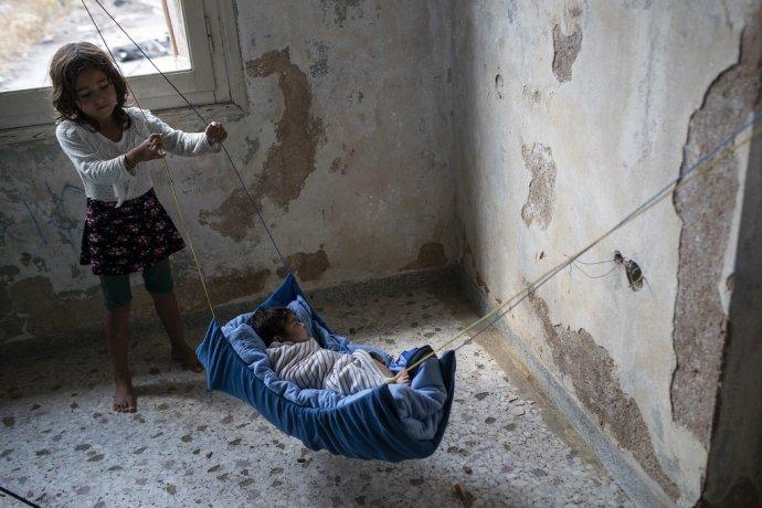 Dievčatko z Afganistanu uspáva dvojmesačné bábätko po tom, ako zhorel tábor Moria. Foto - TASR/AP