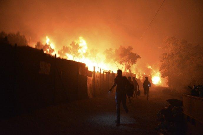 Utečenci a migranti utekajú počas požiaru, ktorý zachvátil preplnený utečenecký tábor Moria na gréckom ostrove Lesbos v stredu 9. septembra 2020. Foto - TASR/AP