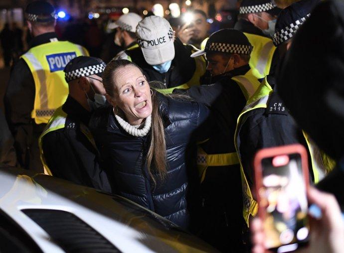 Polícia zatýka ženu počas protestov proti opatreniam na boj s koronavírusom v Londýne. Ilustračné foto - TASR/AP