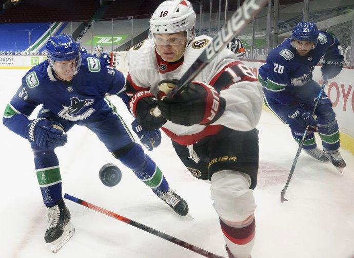 Tim Stützle bojuje o puk proti hráčom Vancouveru. Foto - TASR/AP