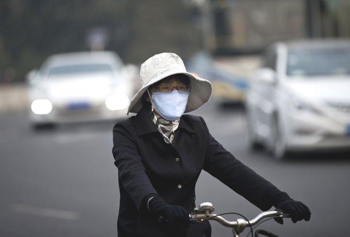 Žena na bicykli s rúškom na tvári v Pekingu 22. októbra 2013. Foto – TASR/AP