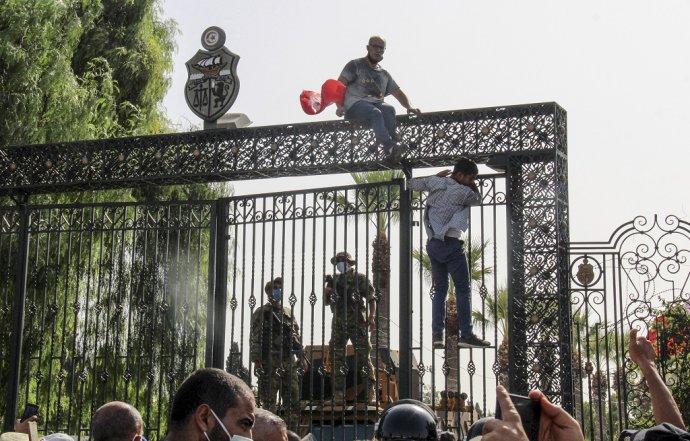 Demonštranti protestujú pred tuniským parlamentom, ktorý strážia vojaci. Foto: TASR/AP