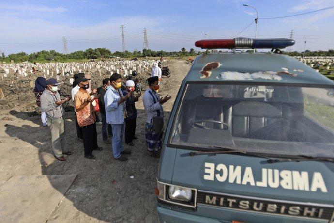 Indonézia je novým epicentrom pandémie. Ľudia sa modlia pred sanitkou, v ktorej leží ich zosnulý príbuzný. Foto - TASR/AP
