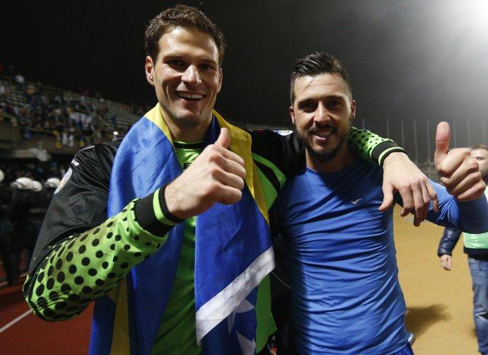 Asmir Begović (vľavo) a Haris Medunjanin sa radujú z víťazstva v Litve, ktorým si Bosna zabezpečila postup na MS 2014. Foto - TASR/AP