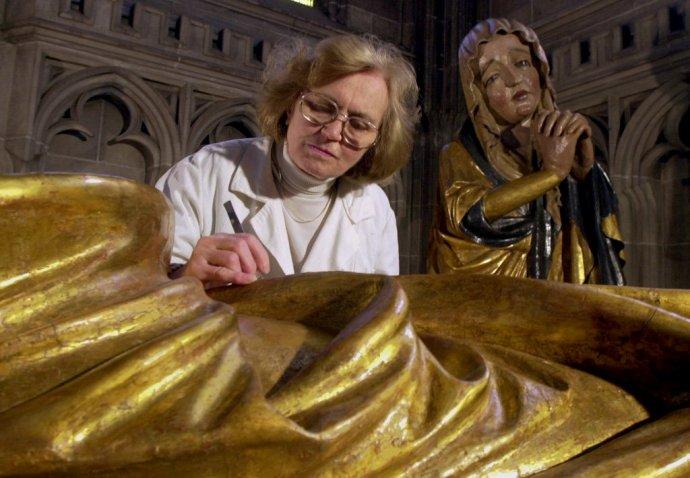 Mária Spoločníková pri reštaurovaní drevených plastík kalvárie na empore oratória v Dóme sv. Alžbety v Košiciach v roku 2000. Foto - TASR